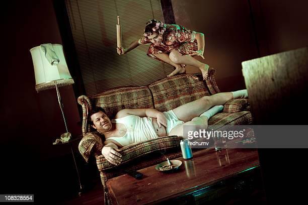 Homem Slob ver televisão enquanto mulher pounces com Rolo da Massa
