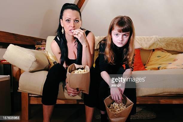 Putzfrau von Mutter und Tochter pigging auf popcorn