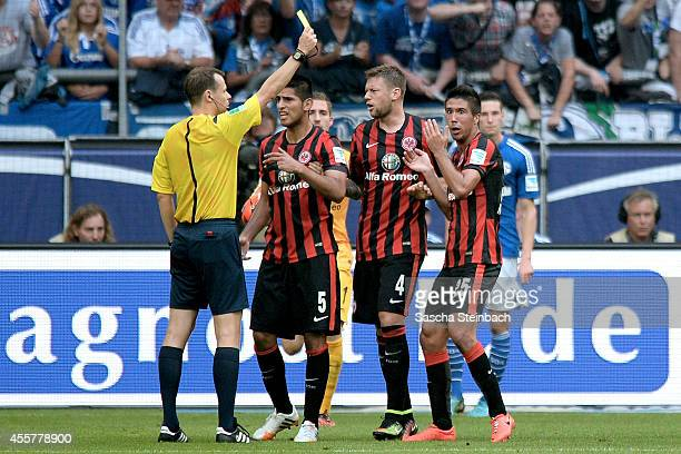 Slobodan Medojevic of Frankfurt is booked yellow card by referee Markus Schmidt during the Bundesliga match between FC Schalke 04 and Eintracht...
