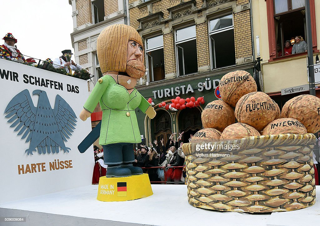 A slogan-bearing float that shows Chancellor Merkel cracking nuts makes its way through carnival revellers during the annual Rose Monday parade on February 8, 2016 in Cologne, Germany. The centuries-old tradition of German carnival occurs in February and runs until Ash Wednesday, the start of Lent, and culminates in Rose Monday celebrations. Police are on added alert this year, particularly in Cologne, due to the New Year`s Eve sex attacks on women that have been attributed to gangs of migrants.