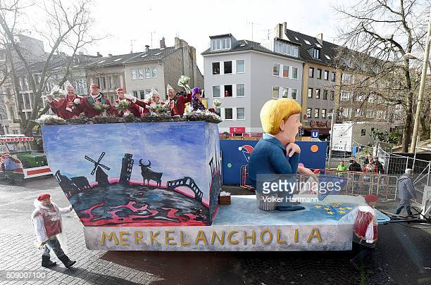 A sloganbearing float that shows German Chancellor Angela Merkel makes its way through carnival revellers during the annual Rose Monday parade on...