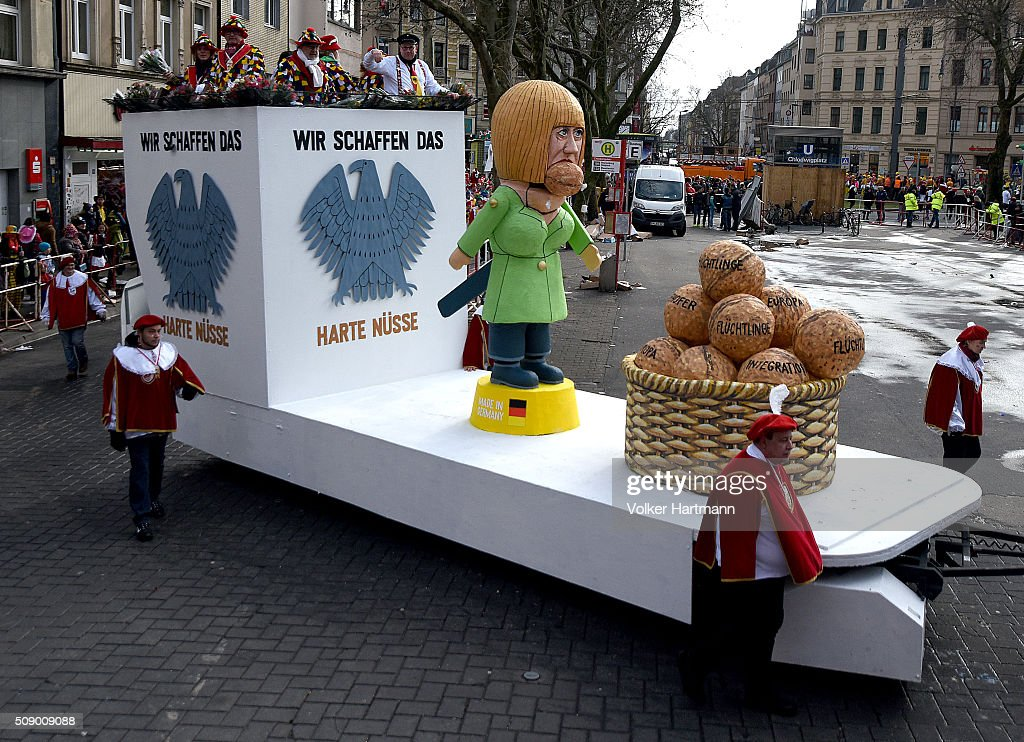 A slogan-bearing float that shows German Chancellor Angela Merkel cracking nuts makes its way through carnival revellers during the annual Rose Monday parade on February 8, 2016 in Cologne, Germany. The centuries-old tradition of German carnival occurs in February and runs until Ash Wednesday, the start of Lent, and culminates in Rose Monday celebrations. Police are on added alert this year, particularly in Cologne, due to the New Year`s Eve sex attacks on women that have been attributed to gangs of migrants.