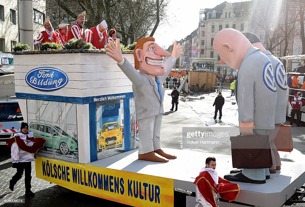 A slogan-bearing float that shows Volkswagen engineers being welcomed by a Ford employee makes its way through carnival revellers during the annual Rose Monday parade on February 8, 2016 in Cologne, Germany. The centuries-old tradition of German carnival occurs in February and runs until Ash Wednesday, the start of Lent, and culminates in Rose Monday celebrations. Police are on added alert this year, particularly in Cologne, due to the New Year`s Eve sex attacks on women that have been attributed to gangs of migrants.