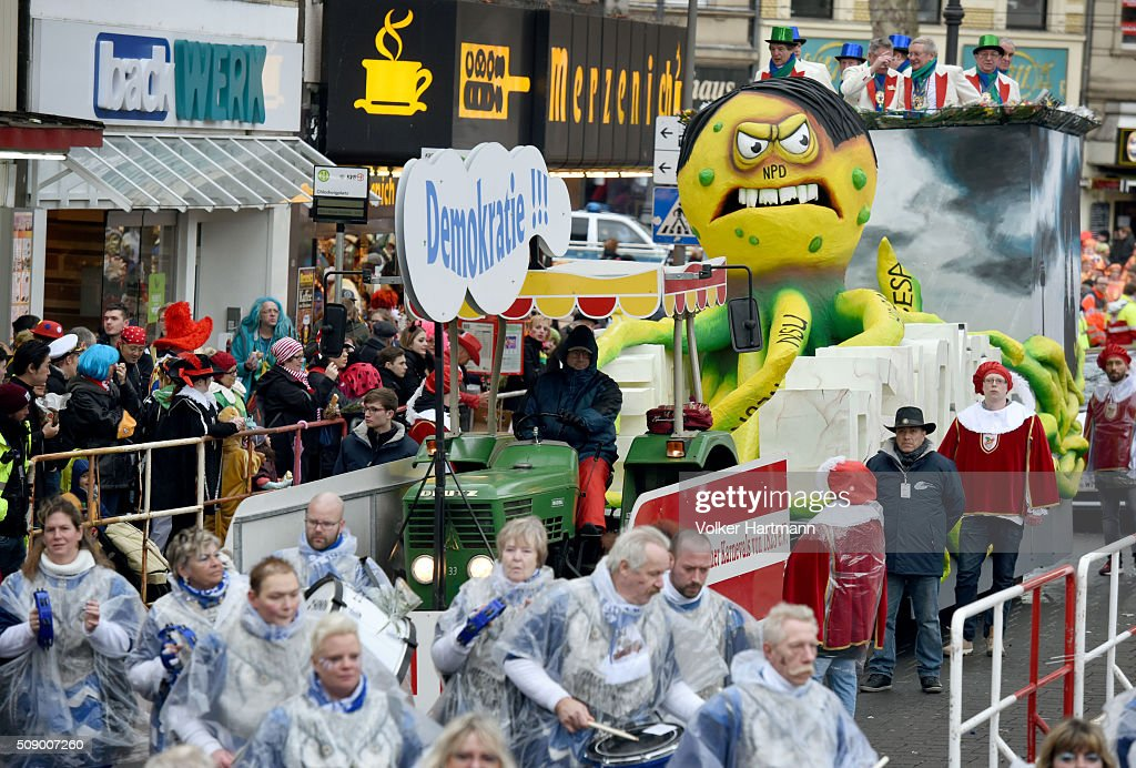 A slogan-bearing float that symbolizes right wing parties attacking the democracy makes its way through carnival revellers during the annual Rose Monday parade on February 8, 2016 in Cologne, Germany. The centuries-old tradition of German carnival occurs in February and runs until Ash Wednesday, the start of Lent, and culminates in Rose Monday celebrations. Police are on added alert this year, particularly in Cologne, due to the New Year`s Eve sex attacks on women that have been attributed to gangs of migrants.