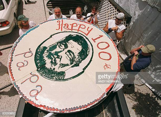 Sloppy Joe's Bar employees load a giant birthday cake onto a back of a truck 20 July 1999 crafted to honor the 100th birthday anniversary of Ernest...