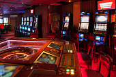 Roulette table and Slot machine. Red lighted casino.
