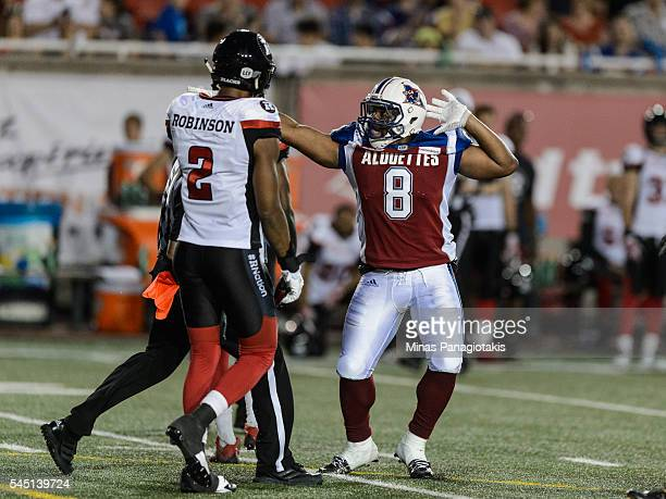Slotback Nik Lewis of the Montreal Alouettes reacts in front of defensive back Jermaine Robinson of the Ottawa Redblacks during the CFL game at...