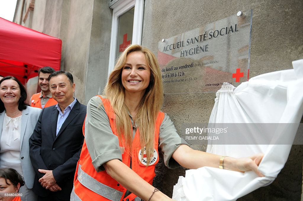 Slovak model and ambassador for the French Croix Rouge (Red Cross) Adriana Karembeu (R) unveils a plaque during the inauguration of an health centre for the needy on May 28, 2016 at the hospital Lagrave in Toulouse, southern France, as part of the Red Cross national days which aims to present the actions of the charity. / AFP / REMY