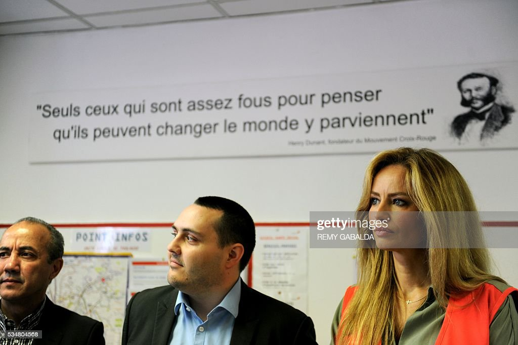 Slovak model and ambassador for the French Croix Rouge (Red Cross) Adriana Karembeu (R) stands in front of a quotes by Swiss humanist and founder of the Red Cross Henry Dunant which translates as 'Only those who are crazy enough to think they can change the world, succeed' during the inauguration of an health centre for the needy on May 28, 2016 at the hospital Lagrave in Toulouse, southern France, as part of the Red Cross national days which aims to present the actions of the charity. / AFP / REMY