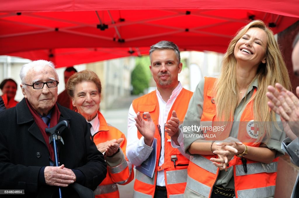 Slovak model and ambassador for the French Croix Rouge (Red Cross) Adriana Karembeu (R) smiles next to founder of the SAMU Pr Louis Lareng (L) during the inauguration of an health centre for the needy on May 28, 2016 at the hospital Lagrave in Toulouse, southern France, as part of the Red Cross national days which aims to present the actions of the charity. / AFP / REMY