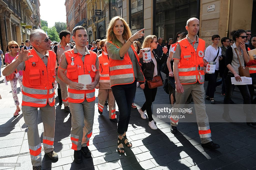 Slovak model and ambassador for the French Croix Rouge (Red Cross) Adriana Karembeu (C) takes part with other volunteers in a money collect for the Red Cross in Toulouse, southern France, on May 28, 2016 as part of the Red Cross national days which aims to present the actions of the charity. / AFP / REMY