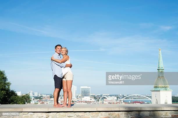Slovakia, Bratislava, happy couple standing on a wall hugging