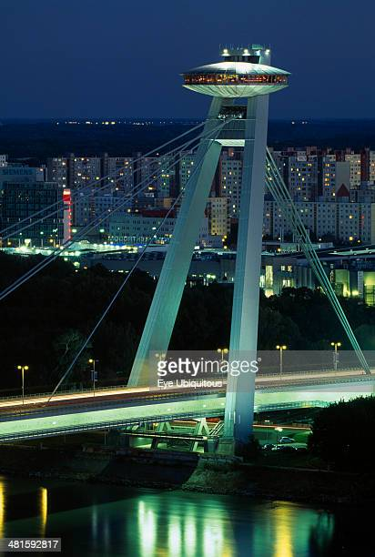 Slovakia Bratislava Novy Most New Bridge topped with restaurant over the River Danube with views towards Petrzalka tower blocks at night with light...