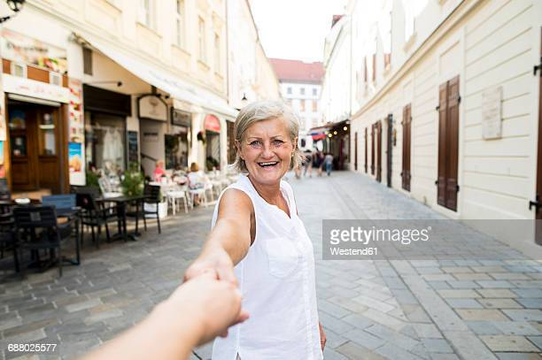 Slovakia, Bratislava, portrait of happy senior woman holding mans hand on the street