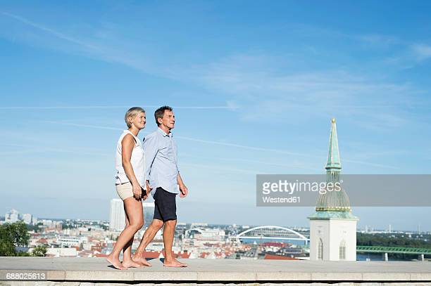 Slovakia, Bratislava, senior couple walking barefoot on a wall in front of the city