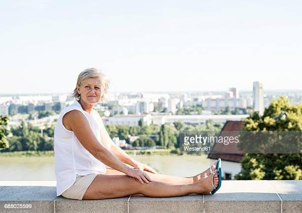 Slovakia, Bratislava, woman sitting on a wall