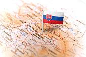 The flag of Slovakia pinned on the map. Horizontal orientation. Macro photography.