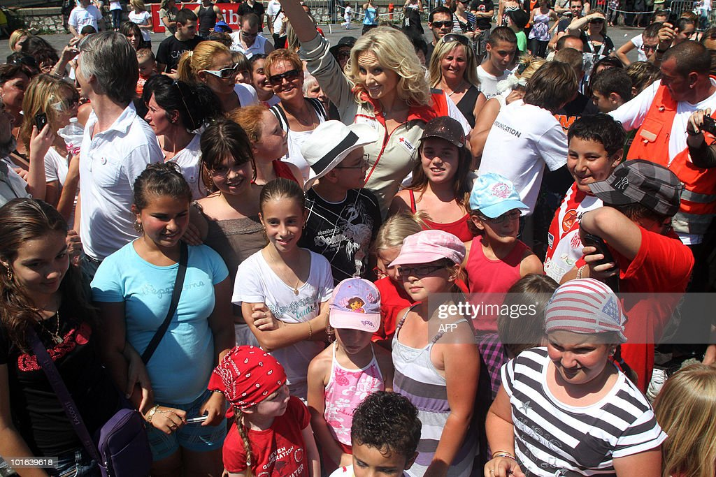 Slovakian born French goodwill ambassador and top-model Adriana Karembeu (background C) takes part in a 'flash mob' as part of the launch of the Red Cross 2010 national fundraising campaign by French Red Cross (Croix Rouge française) on June 5, 2010 in Ales, southern France. A flash mob (for flash mobilisation) is a large group of people who assemble suddenly in a public place, and perform an unusual act for a brief time.
