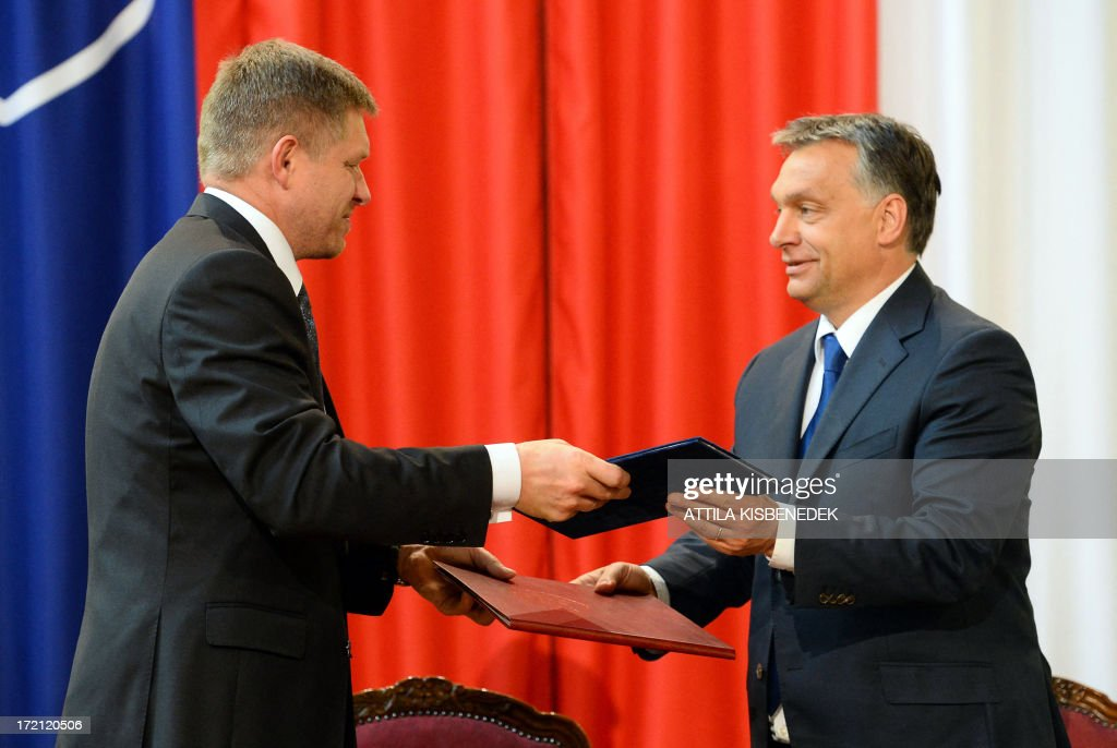 Slovakian Prime Minister Robert Fico (L) and his Hungarian counterpart Viktor Orban (R) change their cooperation agreement in Delegation Hall of the parliament building in central Budapest on July 2, 2013 prior to their joint press conference. Orban meets with Fico for his one-day working visit.