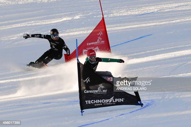Slovakian Zan Kosir clears a gate against italian Aaron March during the Men's Snowboard FIS World Cup Parallel Giant Slalom race in Carezza in the...