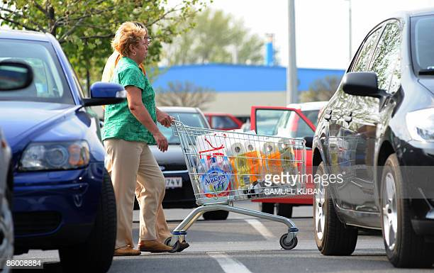 Slovakians push a trolley with their purchases outside a supermarket in the Hungarian town of Mosonmagyarovar about 20 kilometres from Bratislava on...