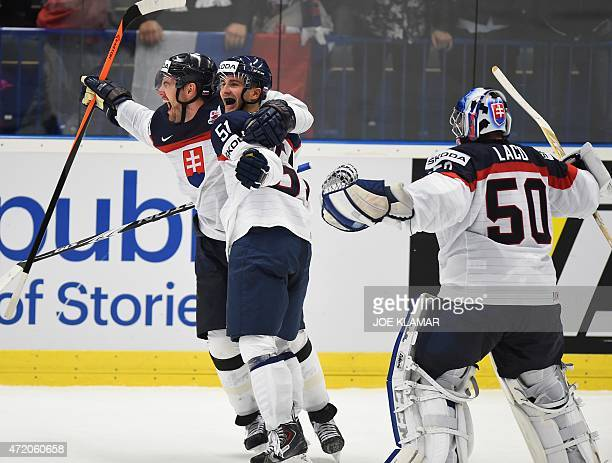Slovakia's Andrej Meszaros and Dominik Granak and goalkeeper Jan Laco celebrate their winning goal scored during the overtime of the group B...