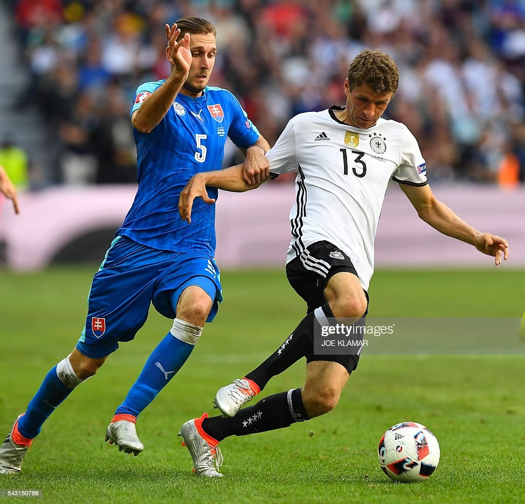Slovakia's defender Norbert Gyomber (L) challenges Germany's midfielder Thomas Mueller during the Euro 2016 round of 16 football match between Germany and Slovakia at the Pierre-Mauroy stadium in Villeneuve-d'Ascq near Lille on June 26, 2016. / AFP / Joe KLAMAR