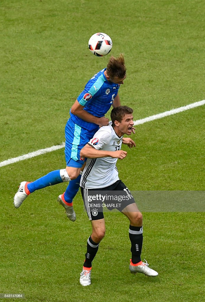 Slovakia's defender Norbert Gyomber (L) vies with Germany's midfielder Thomas Mueller during the Euro 2016 round of 16 football match between Germany and Slovakia at the Pierre-Mauroy stadium in Villeneuve-d'Ascq, near Lille, on June 26, 2016. / AFP / DENIS