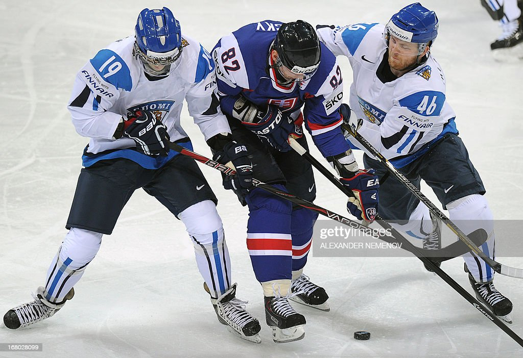 Slovakia's forward Tomas Kopecky (C) is sandwiched between Finland's forward Veli-Matti Savinainen (L) and Finland's defender Janne Jalasvaara (R) during the preliminary round match Finland vs Slovakia of the IIHF International Ice Hockey World Championship in Helsinki on May 4, 2013.