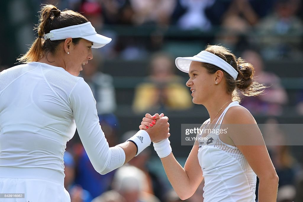 Slovakia's Jana Cepelova (R) shakes hands with Spain's Garbine Muguruza (L) after Cepelova won their women's singles second round match on the fourth day of the 2016 Wimbledon Championships at The All England Lawn Tennis Club in Wimbledon, southwest London, on June 30, 2016. / AFP / GLYN