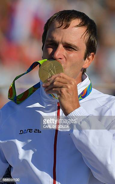Slovakia's Ladislav Skantar kisses his gold medal on the podium of the Men's C2 final canoe slalom competition at the Whitewater stadium during the...