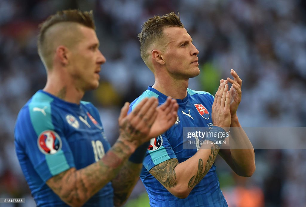 Slovakia's midfielder Juraj Kucka and Slovakia's defender Jan Durica applaud after the Euro 2016 round of 16 football match between Germany and Slovakia at the Pierre-Mauroy stadium in Villeneuve-d'Ascq, near Lille, on June 26, 2016. / AFP / PHILIPPE