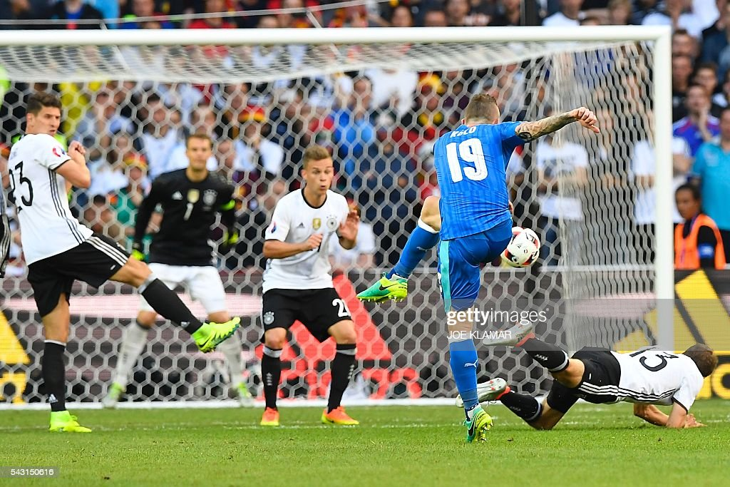 Slovakia's midfielder Juraj Kucka (C) kicks the ball in an attempt to score during the Euro 2016 round of 16 football match between Germany and Slovakia at the Pierre-Mauroy stadium in Villeneuve-d'Ascq near Lille on June 26, 2016. / AFP / Joe KLAMAR