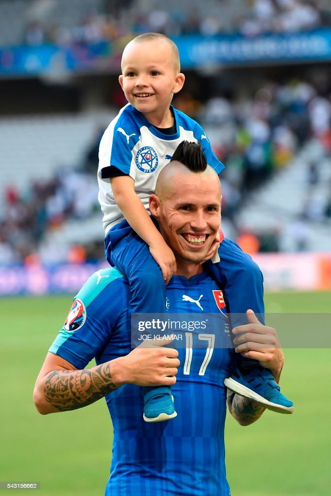 Slovakia's midfielder Marek Hamsik carries his son Lucas at the end of the Euro 2016 round of 16 football match between Germany and Slovakia at the Pierre-Mauroy stadium in Villeneuve-d'Ascq near Lille on June 26, 2016. / AFP / Joe KLAMAR