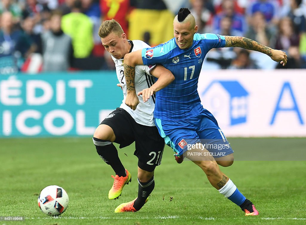 Slovakia's midfielder Marek Hamsik (R) challenges Germany's midfielder Joshua Kimmich during the Euro 2016 round of 16 football match between Germany and Slovakia at the Pierre-Mauroy stadium in Villeneuve-d'Ascq near Lille on June 26, 2016. / AFP / PATRIK