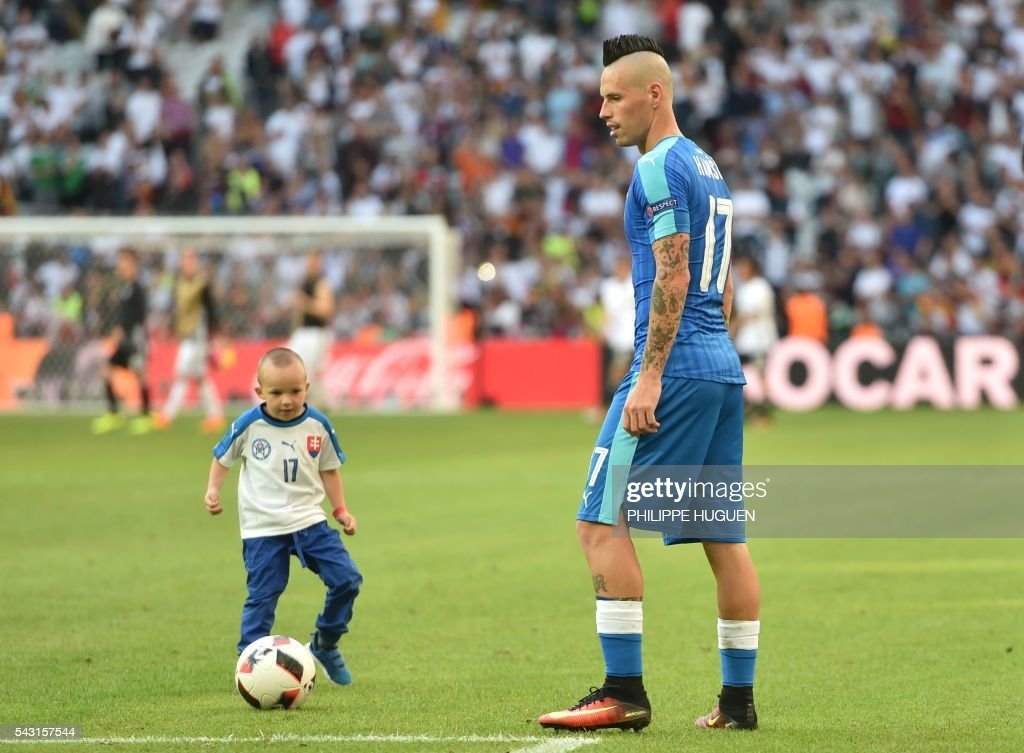 Slovakia's midfielder Marek Hamsik plays with his son Lucas after the Euro 2016 round of 16 football match between Germany and Slovakia at the Pierre-Mauroy stadium in Villeneuve-d'Ascq, near Lille, on June 26, 2016. / AFP / PHILIPPE