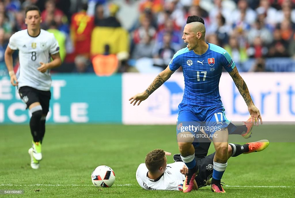 Slovakia's midfielder Marek Hamsik (R) reacts after being challenged by Germany's midfielder Joshua Kimmich (back R) during the Euro 2016 round of 16 football match between Germany and Slovakia at the Pierre-Mauroy stadium in Villeneuve-d'Ascq near Lille on June 26, 2016. / AFP / PATRIK