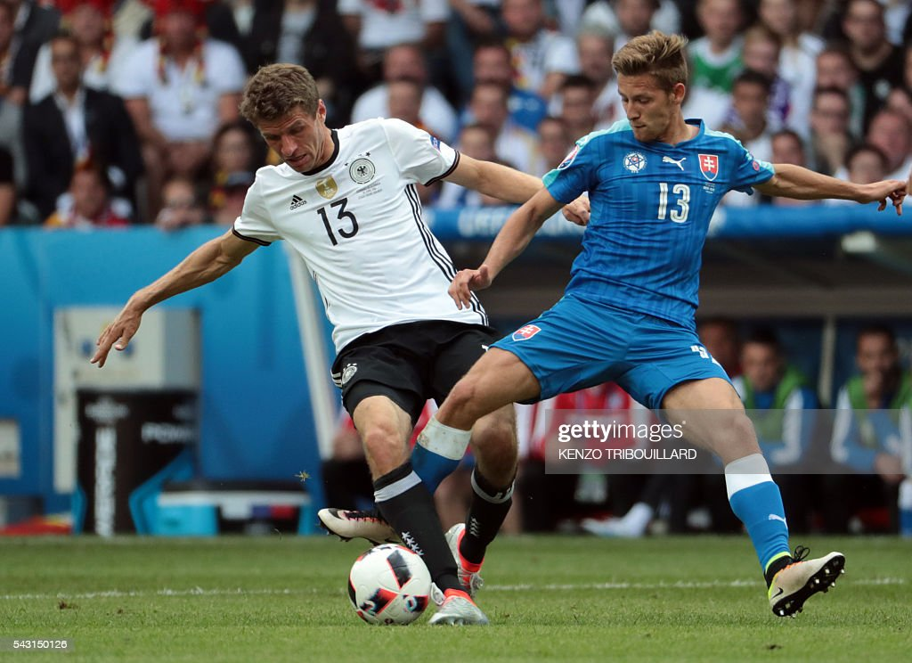 Slovakia's midfielder Patrik Hrosovsky (R) challenges Germany's midfielder Thomas Mueller during the Euro 2016 round of 16 football match between Germany and Slovakia at the Pierre-Mauroy stadium in Villeneuve-d'Ascq near Lille on June 26, 2016. / AFP / KENZO
