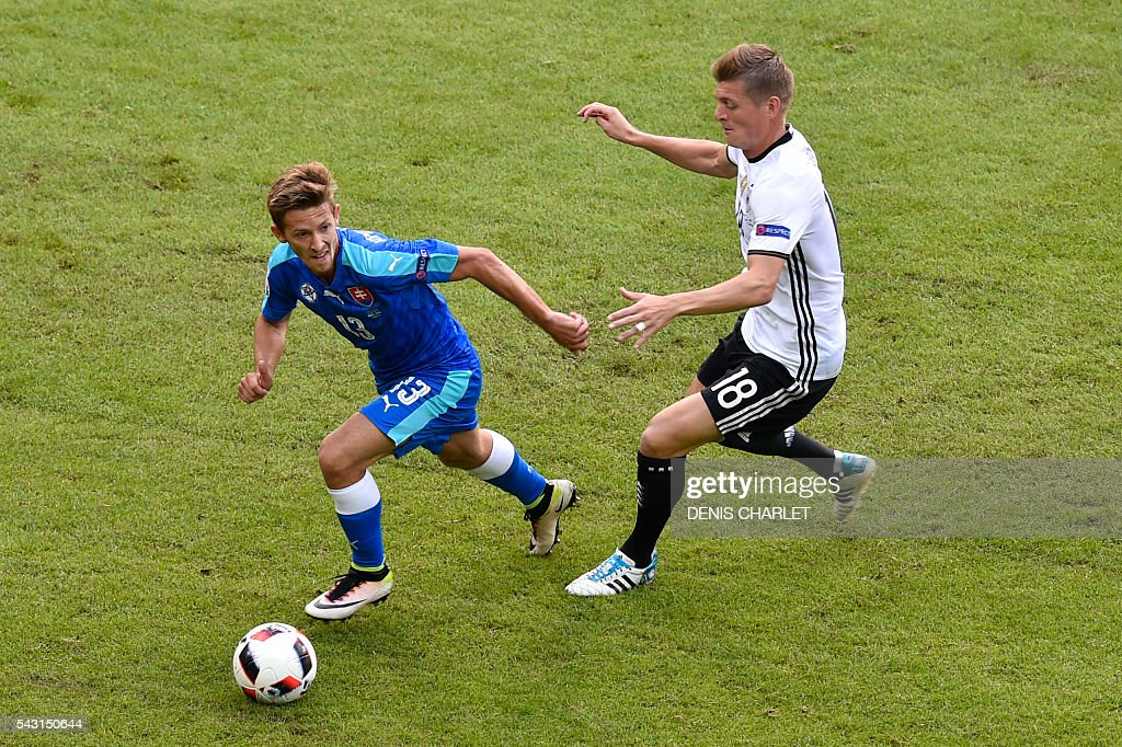 Slovakia's midfielder Patrik Hrosovsky (L) vies with Germany's midfielder Toni Kroos during the Euro 2016 round of 16 football match between Germany and Slovakia at the Pierre-Mauroy stadium in Villeneuve-d'Ascq, near Lille, on June 26, 2016. / AFP / DENIS
