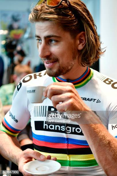 Slovakia's Peter Sagan drinks a coffee at a bike store prior to giving a press conference in Dusseldorf Germany on June 29 two days before the start...