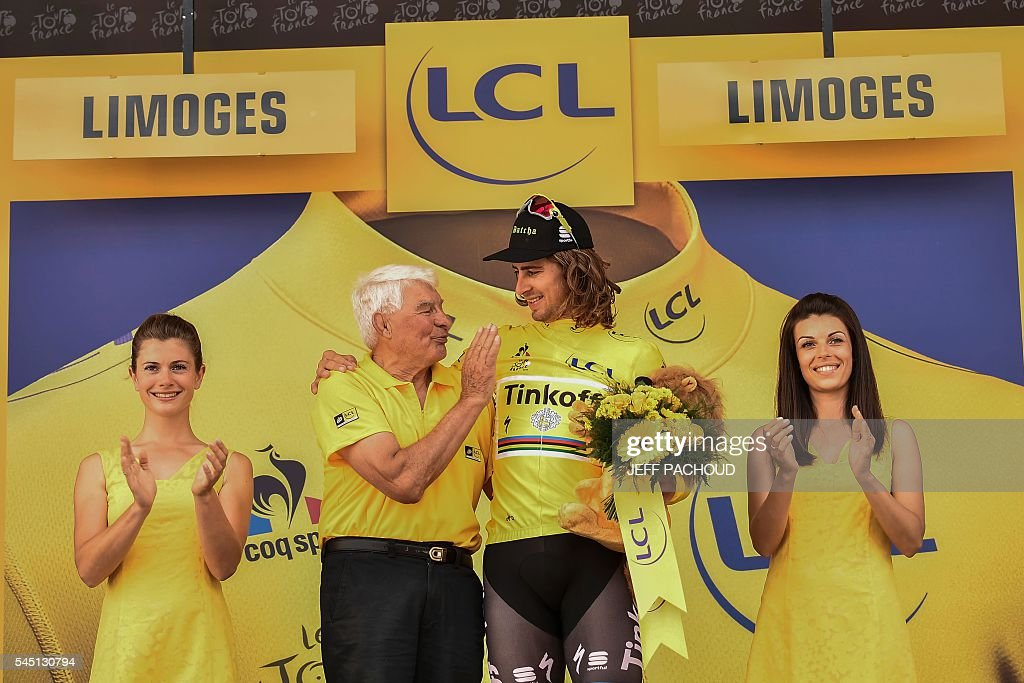 Slovakia's Peter Sagan (R) is congratulated by French former cyclist Raymond Poulidor (L) as he celebrates his overall leader yellow jersey on the podium at the end of the 237,5 km fourth stage of the 103rd edition of the Tour de France cycling race on July 5, 2016 between Saumur and Limoges. / AFP / jeff pachoud