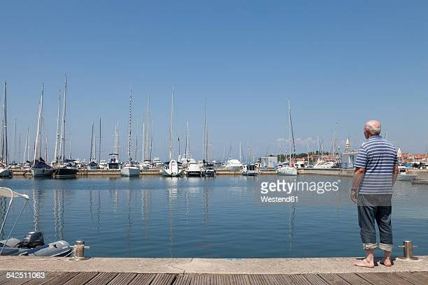 Slovenia, Istria, Izola, man at seashore with marina