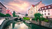 Slovenia Ljubljana Tromostovje Ljublianica river Church with bridge and boat.