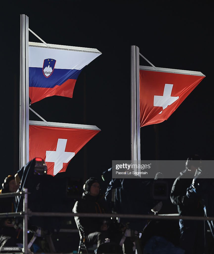 A Slovenian and a Swiss flag are raised on the same flagpole for joint gold medalists Tina Maze of Slovenia and Dominique Gisin of Switzerland and another Swiss flag is raised for bronze medalist Lara Gut of Switzerland during the medal ceremony for the Alpine Skiing Women's Downhill on day five of the Sochi 2014 Winter Olympics at Medals Plaza on February 12, 2014 in Sochi, Russia.