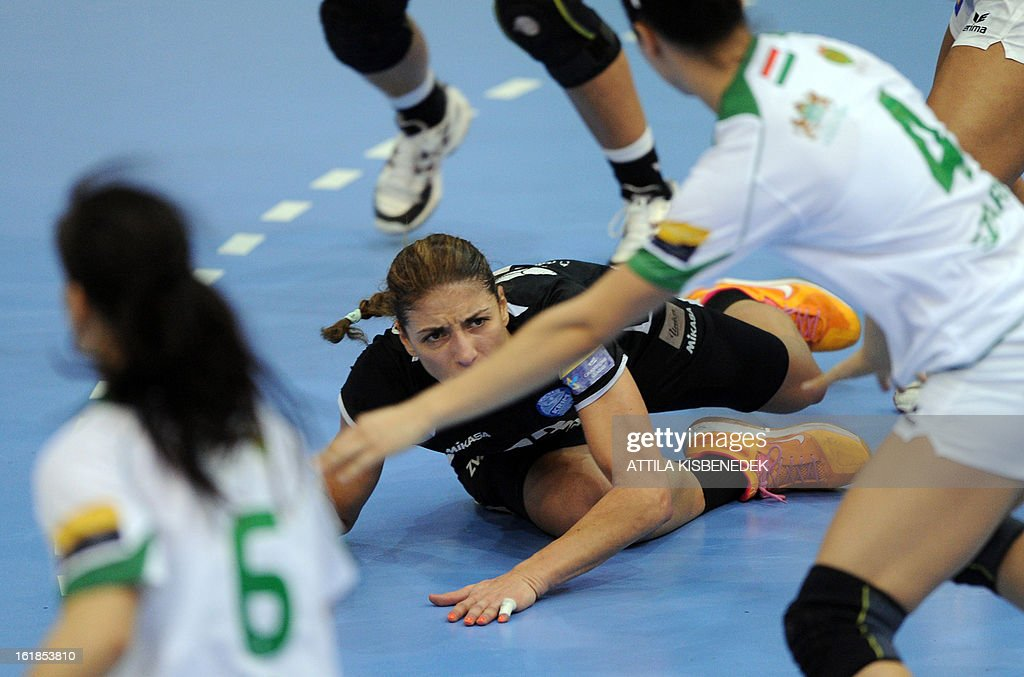 Slovenian Andrea Penezic (C) of RK Krim Mercator lays on the floor between Hungarian defenders of FTC Rail Cargo Hungaria in the local sports hall of Dabas on February 17, 2013 during their EHF Women's Champions League handball match.