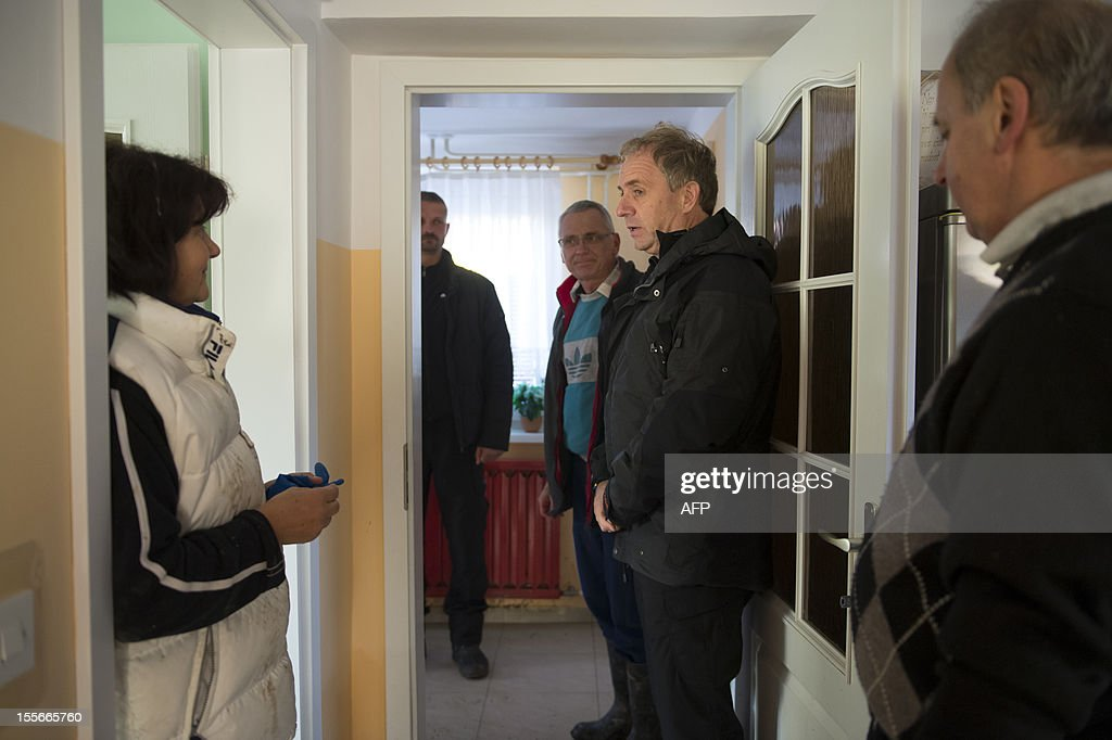 Slovenian Defence Minister Ales Hojs (2nd R) speaks to flood victims in Dogose, some 10 km south-east of Maribor, as the Drava river, a main tributaries of the Danube, rose significantly after days of heavy rains in Slovenia on November 6, 2012.