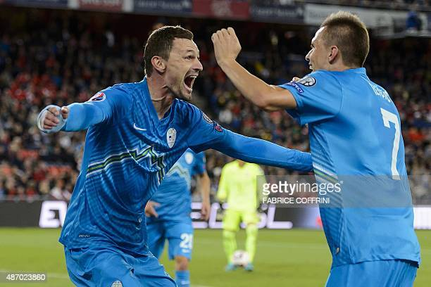Slovenian forward Milivoje Novakovic celebrates with team mate midfielder Josip Ilicic after he scored the team's first goal during the Euro 2016...
