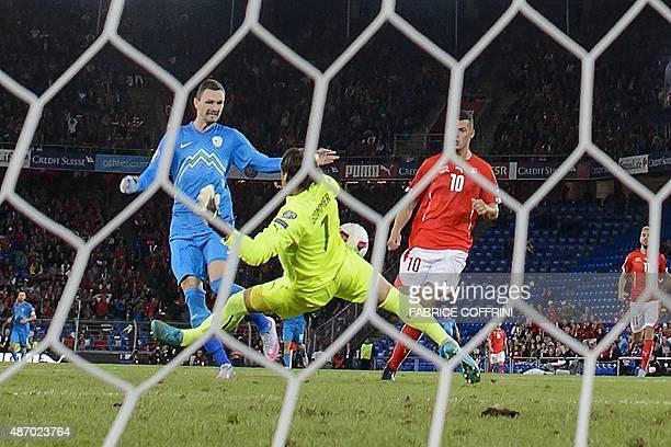 Slovenian forward Milivoje Novakovic scores tes team's first goal against Swiss Goalkeeper Yann Sommer during the Euro 2016 qualifying football match...