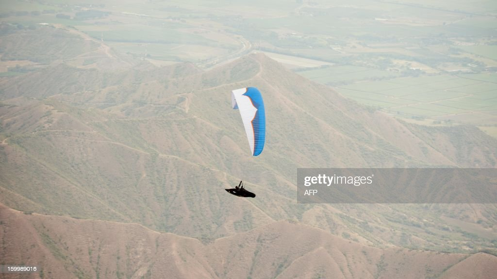 Slovenian paraglider pilot Dusan Oroz flies above the mountains in Roldanillo, Valle del Cauca department, Colombia, during the Paragliding World Cup Superfinal, on January 24, 2013. The competition is taking place for the first time in Colombia and involves the 140 world's best pilots from 32 countries. AFP PHOTO / Luis ROBAYO