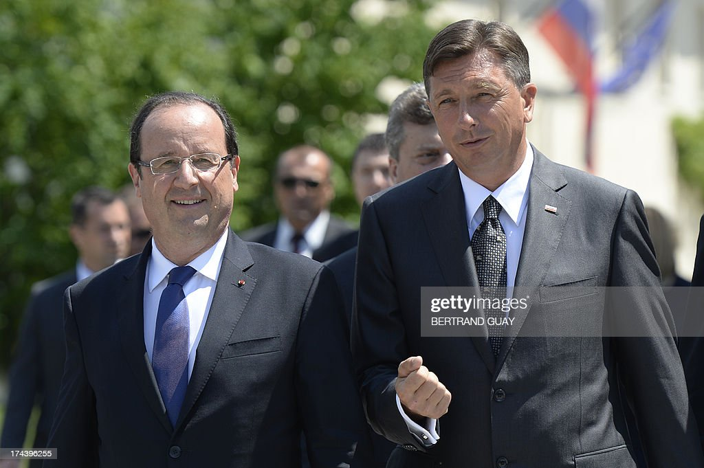 Slovenian President Borut Pahor speaks to his French counterpart Francois Hollande after posing for a group photo during The Leaders' Meeting of Brdo Process in Brdo Pri Kanju on July 25, 2013. The presidents of eight western Balkans countries along with French president Francois Hollande met in Slovenia at an unprecedented summit aimed at promoting cooperation and further EU's enlargement in the region. The summit was organized by the presidents of the only two former Yugoslav states that joined the EU, Slovenia's Borut Pahor and Croatia's Ivo Josipovic, and backed by the French president underlining the need for reforms for all Balkans states that would like to join the EU.